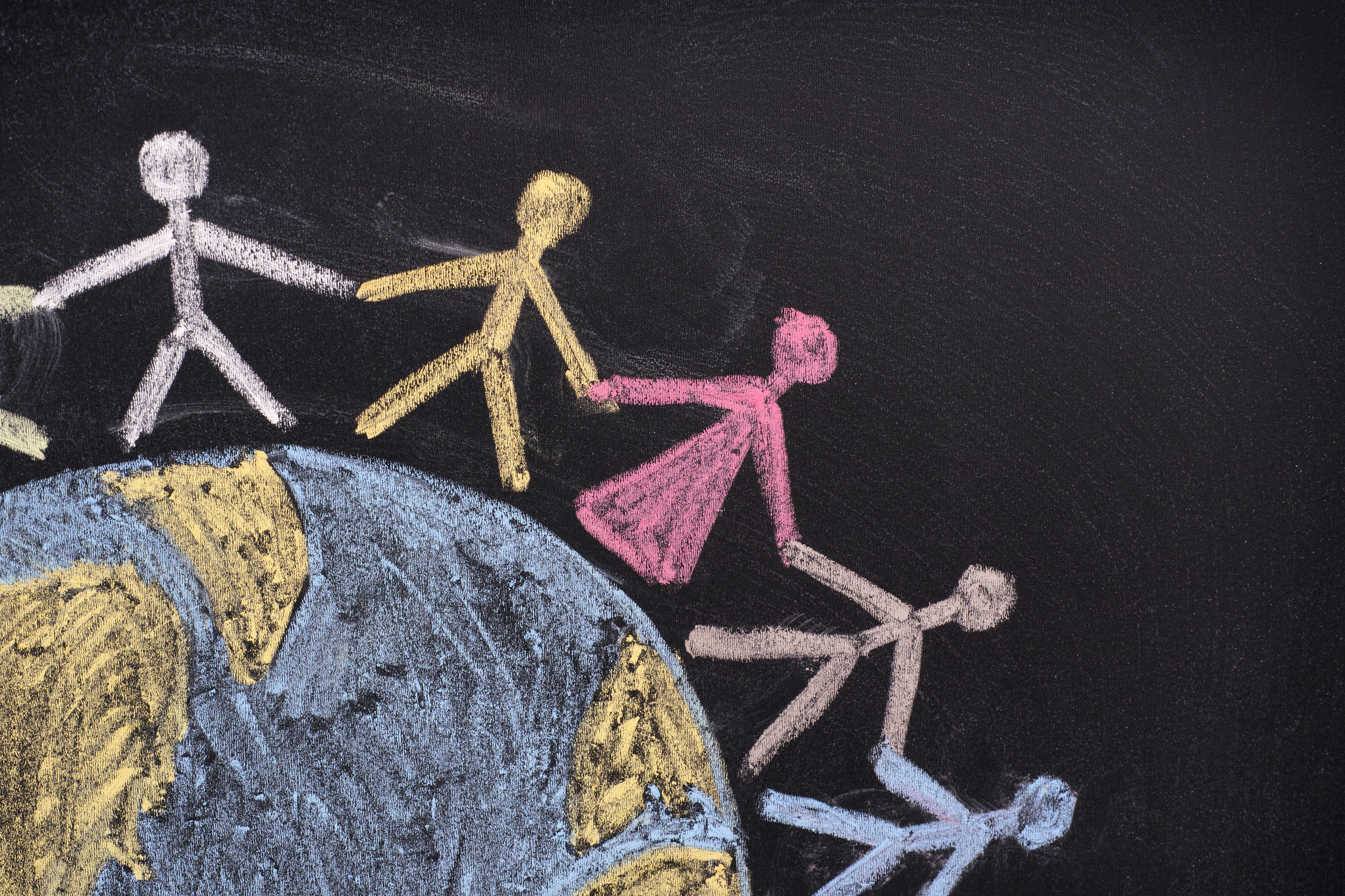 Chalk picture of a world with stick figures holding hands around it